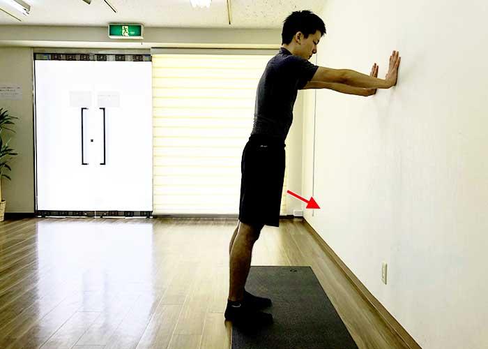 ①壁に向かって立ち、両手のひらを壁につける。