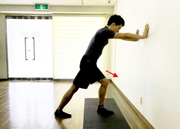 ②右脚を一歩後ろに引き、左膝は曲げる。右脚のつま先を前に向け、かかとが床から浮かないようにして、体重を壁側にかける。(両手で壁を押す)